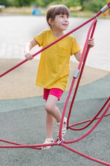 Adorable 6 years old girl in the yellow t-shirt on the playground.