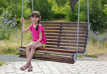 Poster de jardin Doux monstres cute girl on a swing in the park