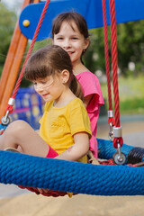two little girls on a swing in the park