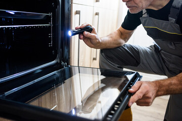 Cropped shot of aged repairman in uniform working, examining broken oven in the kitchen using...