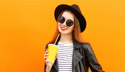 portrait of young woman with cup of juice wearing a black round hat, sunglasses over orange wall background