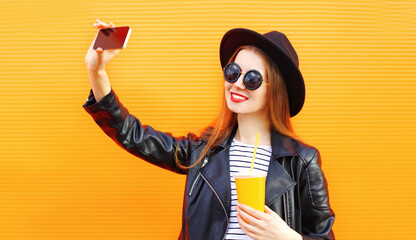 Happy smiling young woman taking selfie picture by phone with cup of juice over orange wall background