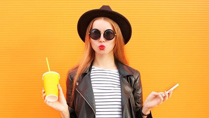 Close up portrait young woman blowing red lips sending sweet air kiss with cup of juice and smartphone over orange wall background