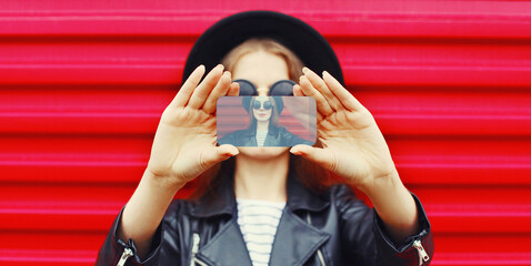 Close-up woman taking selfie picture by smartphone over wall background