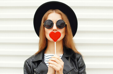 Close up sweet portrait young woman covering her lips with red heart shaped lollipop