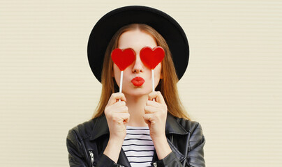 Close up portrait young woman covering her eyes with red heart shaped lollipop blowing lips sending sweet air kiss