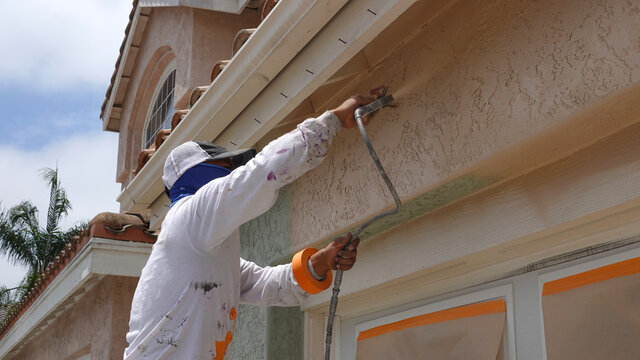 Professional contractor using a spray paint gun to paint the stucco on a home