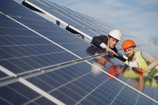 Businessman and worker near solar energy batteries. Business client showing photovoltaic detail to foreman. Two men making deal.