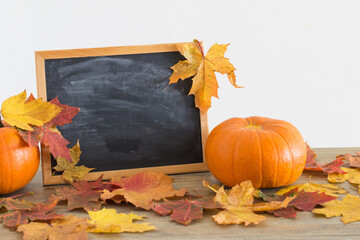 chalkboard and autumnal leaves on wooden table