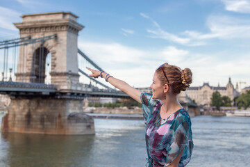 Happy woman pointing to Chain Bridge at Budapest, Hungary
