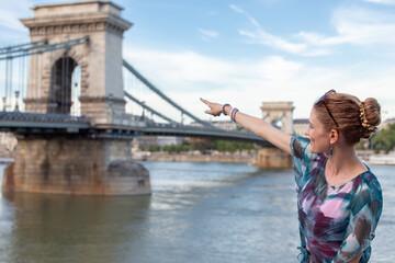 Young woman pointing to Szechenyi Chain Bridge at Budapest, Hungary