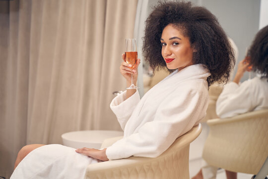 Restful smiling curly haired lady having pleasurable time in spa