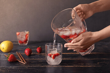 Woman pouring fresh strawberry lemonade in glass on table