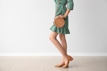 Beautiful young woman with wicker bag near light wall