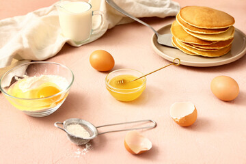 Ingredients for pancakes on color background