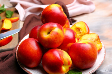 Plate with sweet ripe nectarines on table
