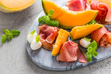 Traditional Italian appetizer - Prosciutto with cantaloup melon, mozzarella and basil