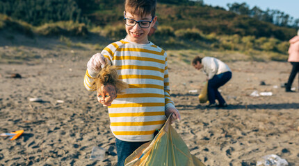 Boy showing doll head while volunteer group cleans the beach