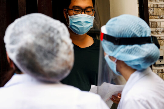 Healthcare workers talk to a local resident near the house of a coronavirus disease (COVID-19) patient as they investigate infection links in Hanoi