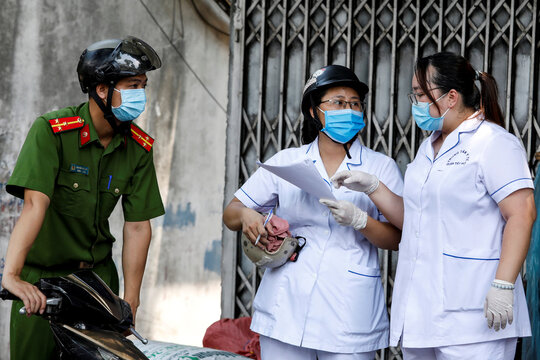 A police officer talks to healthcare workers at a lane near the house of a coronavirus disease (COVID-19) patient while they investigate infection links in Hanoi, Vietnam