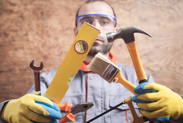 Worker holding hammer, saw, brush, level, wrench, pliers. Working tools