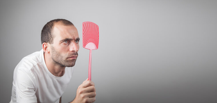 Caucasian man holding a fly swatter.