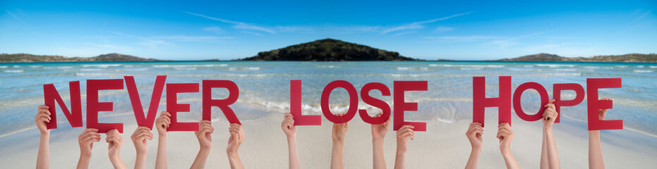 People Hands Holding Colorful English Word Never Lose Hope. Ocean And Beach As Background