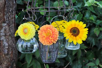 Gartendekoration mit Sommerblumen in Glasvasen hängend am Kräutertrockner