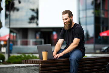 Young handsome bearded man sitting on the park bench using laptop outdoors