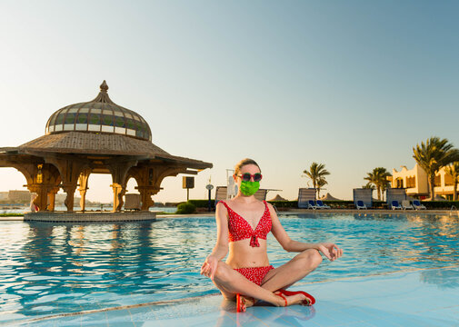 young woman in red swim suit and protective green mask sitting near empty beach pool at tropical resort sunset