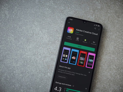 Lod, Israel - July 8, 2020: Adobe Creative Cloud app play store page on the display of a black mobile smartphone on ceramic stone background. Top view flat lay with copy space.
