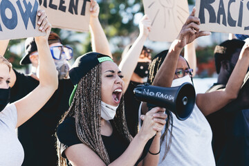 People from different ages and races protest on the street for equal rights - Demonstrators wearing face masks during black lives matter fight campaign - Main focus girl's face holding megaphone