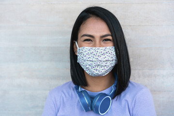 Lating millennial girl smiling in front of camera while wearing face protective mask - Health care...