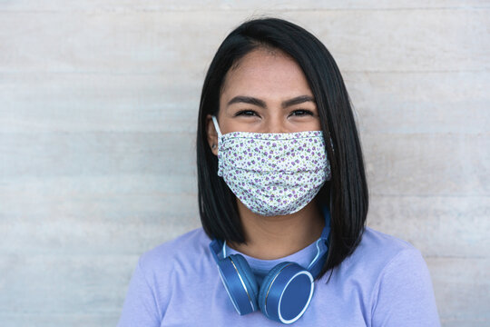 Lating millennial girl smiling in front of camera while wearing face protective mask - Health care and new coronavirus lifestyle concept - Focus on face