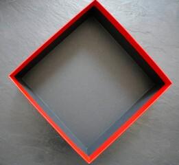 Leere schwarze Box mit rotem Rand auf dunklem Hintergrund