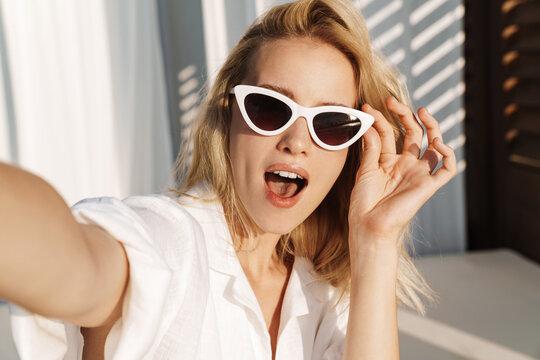 Image of seductive surprised woman in sunglasses taking selfie photo