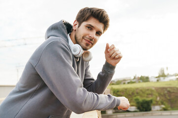 Image of athletic sportsman looking at camera while leaning on railing
