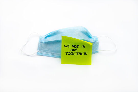 Single use medical face mask with handwritten message on post-it note We Are In This Together isolated over white background, coronavirus protection concept