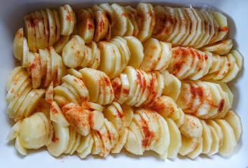Rohe Kartoffelscheiben mit Paprikapulver bestreut zum Überbacken