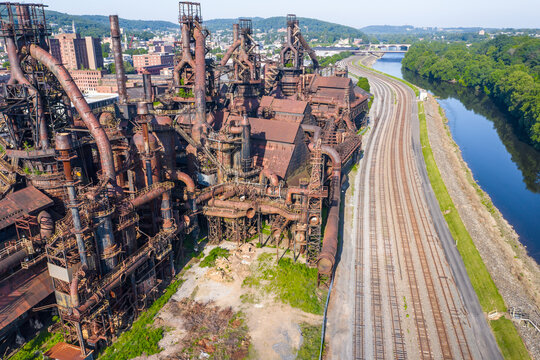 Aerial of abandoned steel factory in Pennsylvania with train tracks and a river alongside.