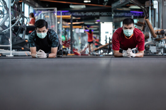 young mam and friend working out wearing surgical mask & latex rubber gloves, COVID-19 pandemic social distancing rules while working out in  a gym, new normal & social distancing concept