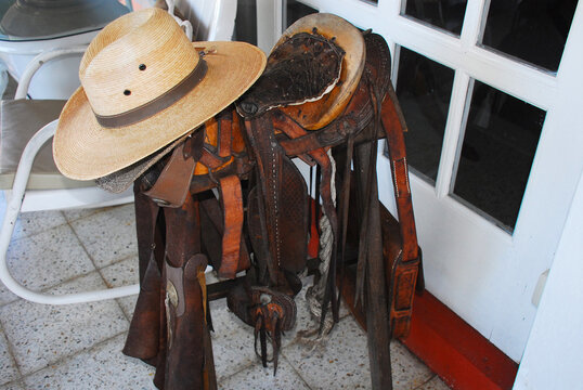 Guatemala- A Saddle, Bag and Hats at Rest on a Porch