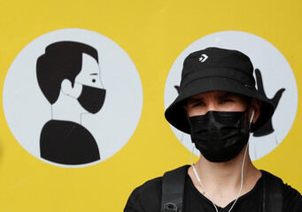 A man wearing a protective face mask stands in front of a social poster in Kyiv