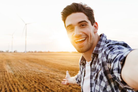Happy man taking selfie against the industrial landscape