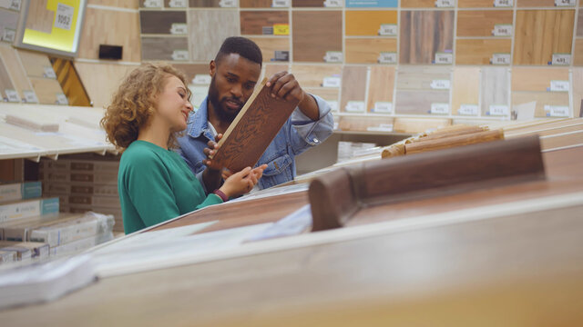Diverse couple looking at parquet board for home flooring in store