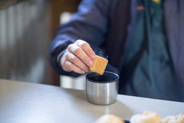 Dunking biscuit in a cup of tea