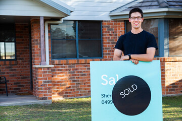 grinning young man with sold sign in front of newly purchased house