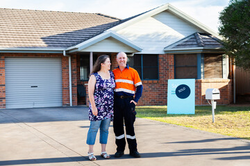 Happy middle aged couple standing infront of house with sold real estate sign
