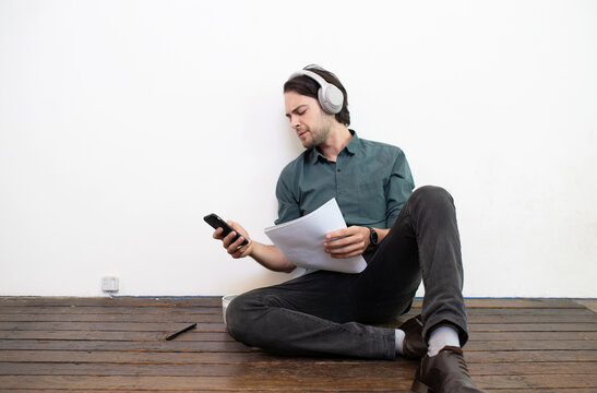 Man, sitting on floor with head-phones on checking iPhone