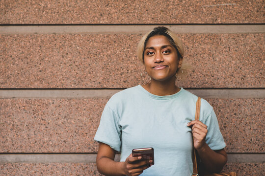 happy young woman leading against wall with mobile phone